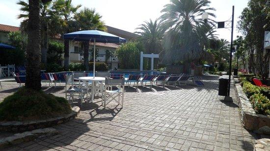 LD Palm Beach : Pileta con reposeras y mesas