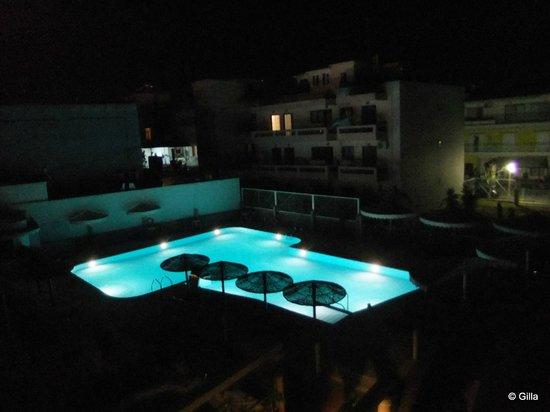 Astron Hotel : Poolen på kvällen sedd från vår balkong.