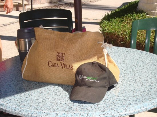 Villa del Palmar Beach Resort & Spa: Casa Velas bag & Trip Advisor hat on pool table