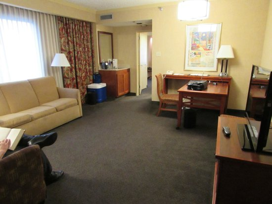 Embassy Suites by Hilton San Antonio Airport: Spacious sitting room with chairs, desk, sofabed, TV, and bar sink.