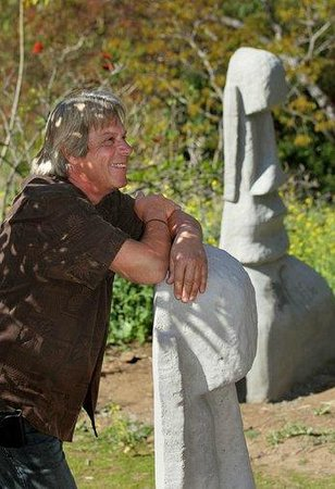 Alta Vista Gardens : Environmental Artist Bryan Morse leans of one of his Easter Island sculptures