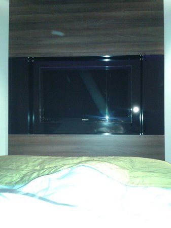 PURO Hotel: Integrated tv/sound system/computer screen. Plug beside bed to connect laptop to tv.