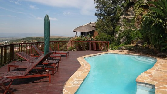 Isandlwana Lodge: A reasonably long swimming pool - with a panoramic view beyond and the cliff behind.