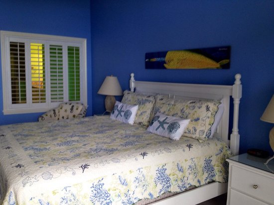 TOPS'L Beach & Racquet Resort : King bed and plantation shudder window into the spa bathroom