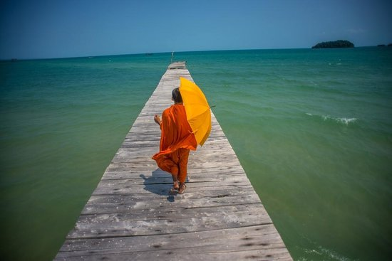Île privée de Song Saa : A monk walking down a pier