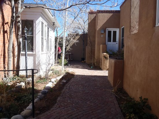 Las Palomas Inn Santa Fe : Path in the courtyard; there is a fireplace at the back.