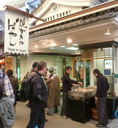 Front of Yakigaki No Hayashi with staff grilling Oysters on the street.