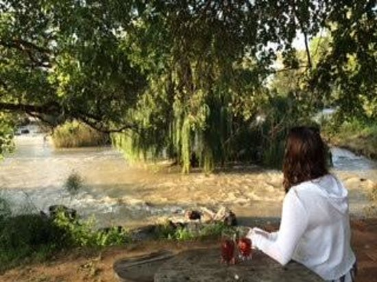 Waterfront Guest House: Seating area outside the property. River in full flow.
