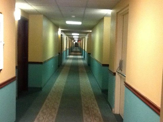 Fifth Season Inn & Suites: Rear rooms - taken from the hall doorway. Carpet torn, paint and wallpaper pealing.
