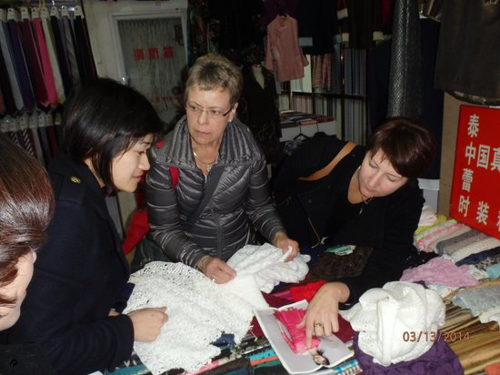 Shanghai, China: The dressmaker (left) and MJ (right) help Nancy pick out material for a dress that was made in 2