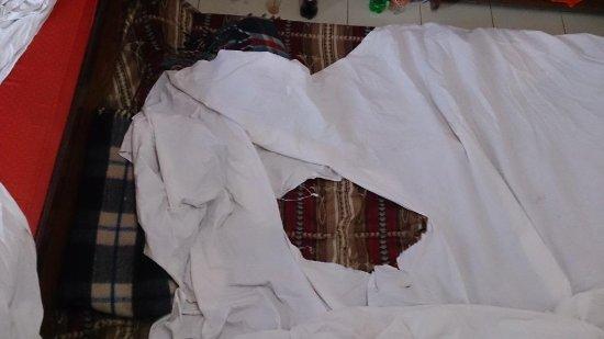 Hotel JK International: torn bedsheet