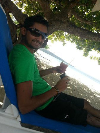 Radisson Grenada Beach Resort: bf sitting under a tree on the beach with a bloody mary