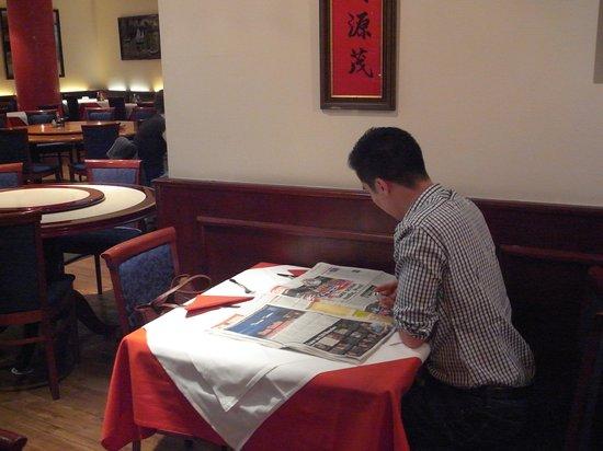 Kam Yi: 後ろで新聞を読んでる愛想ない店主