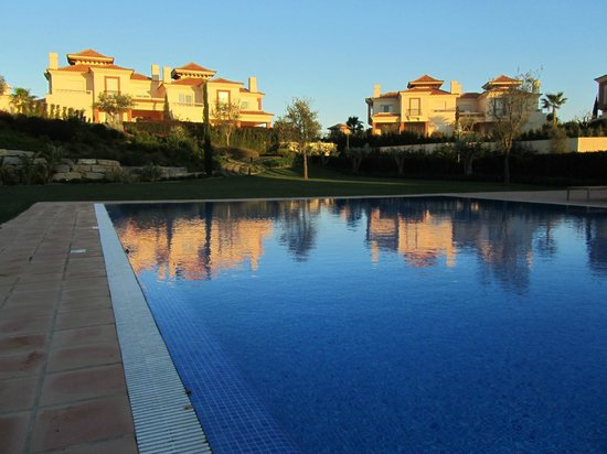 Monte Rei Golf & Country Club : Atardecer con las villas al fondo desde la piscina.