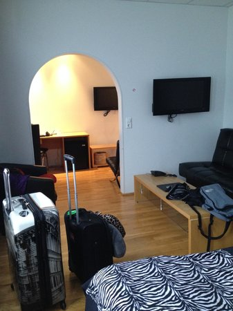 4th Floor Hotel : Two TV's, a sofa and a desk.