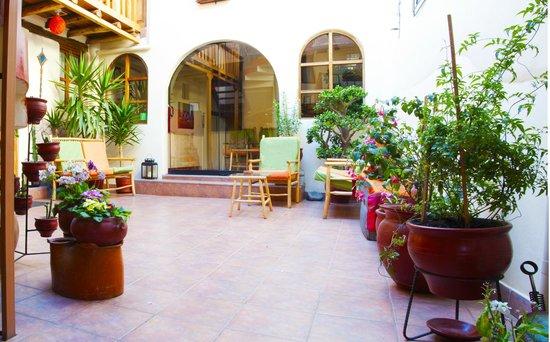 Hotel Casona les Pleiades: Patio central con alrededores de plantas y flores tipicas de Cusco