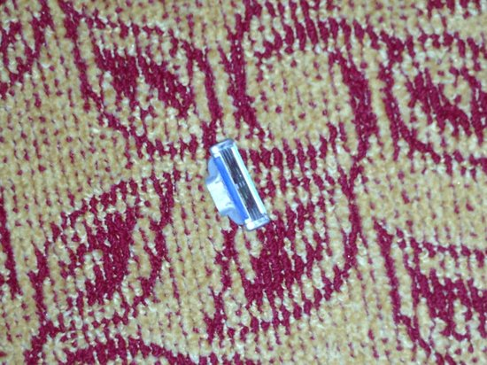 McCamly Plaza Hotel: disposable razor head on the floor of the hotel room