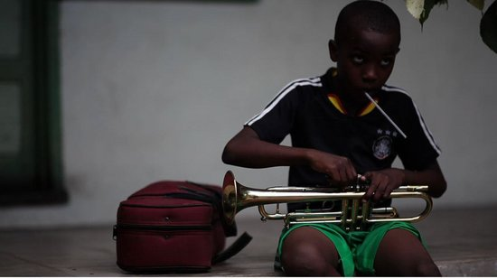 Trench Town Culture Yard : a youngster getting ready for music lessons