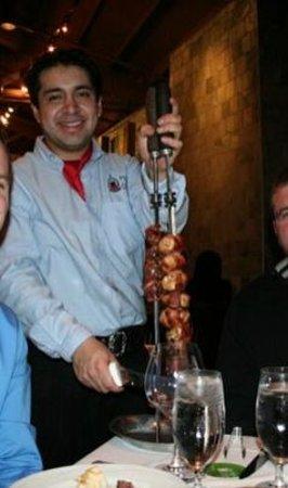 Fogo de Chao Brazilian Steakhouse: официант предлагает порцию бразильского шашлычка