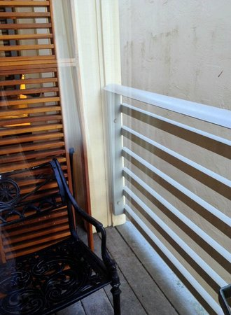 Waters Edge Hotel : Our tiny deck with a louvered partition and a dirty wall next door.