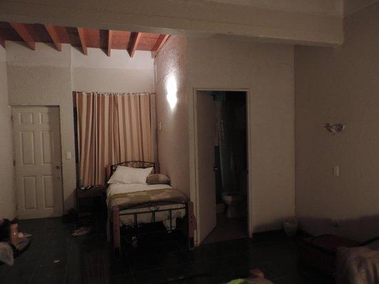 Hotel Rapa Nui : Habitación triple, cama y baño junto a la puerta.