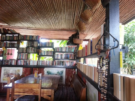 Cafe Rico: shelves full of books in the middle of a tropical garden