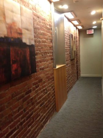 Charlesmark Hotel: Cool exposed brick  and metal /wood decor in narrow hallway