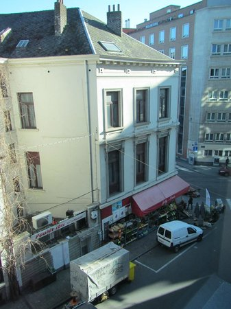 Four Points by Sheraton Brussels: Looking out our window to the right on the small stree with a shop at the corner