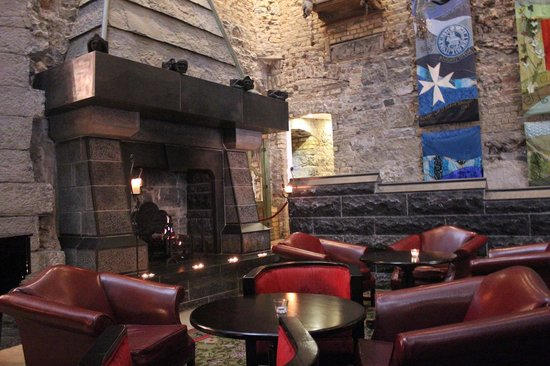 Clontarf Castle Hotel: Fireplace and seating area in lobby