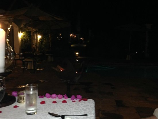 The Manor at Ngorongoro: The table for our final dinner was set poolside with rose petals