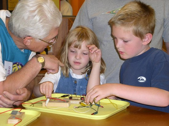 ScienceWorks Hands on Museum: Volunteer helping guests with an electrical circuits activity.
