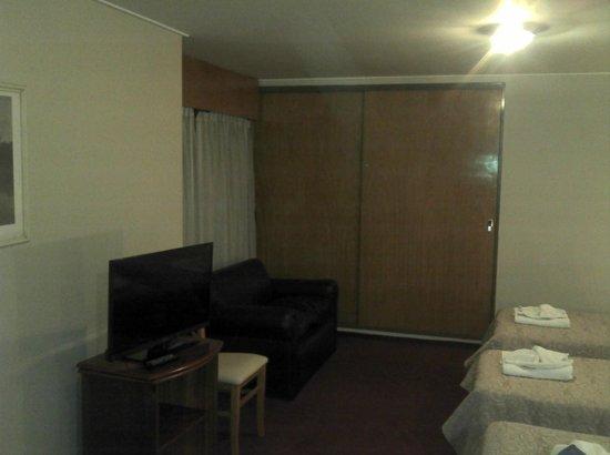 Docta Suites Aparthotel: Televisor, sofá y armario