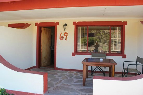 Namib Desert Lodge : ロッジスタイルの客室玄関 テーブルと椅子あり。
