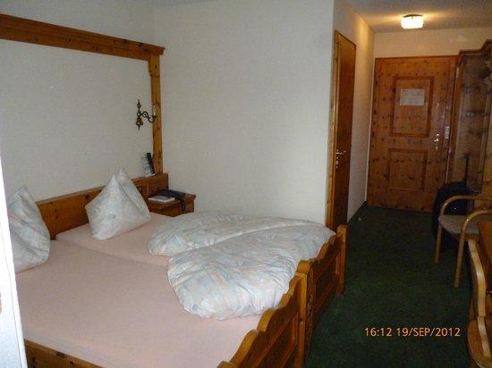 Sardona Hotel: Bed, and hall with toilet entrance