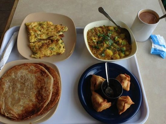 TUNTUN's Cafe: Clockwise from top left- Omelette with chilli, Potato curry, singaras and chutney, and parathas.