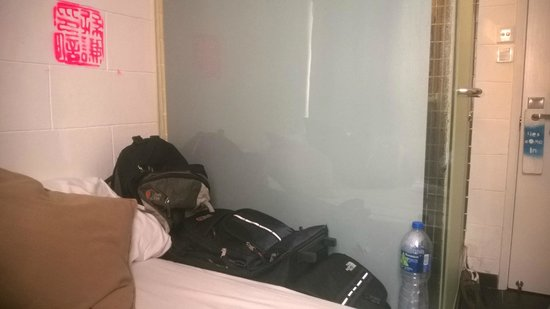 Just Inn: Photo of the bathroom from the bed and of the place where we store our luggage.