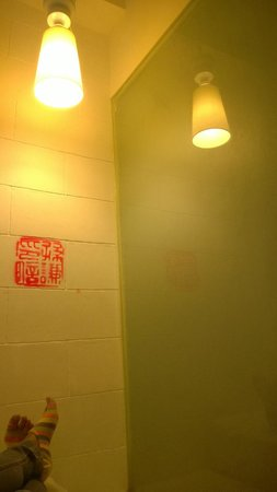Just Inn: Simple artwork in our room and a picture of the light beside the glass wall of the bathroom.