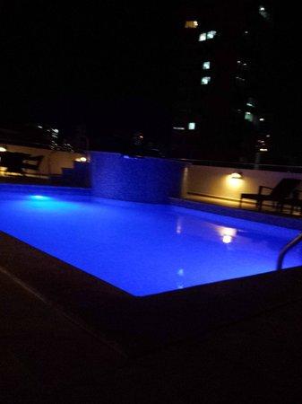 Tryp by Wyndham Panama Centro: Vista noctura de la piscina del hotel con la ciudad al fondo