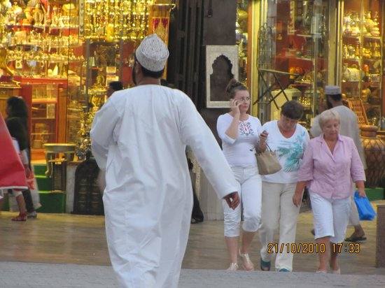Tourists and a local cross paths in the famous Muttrah Souq, facing the Muttrah Corniche.