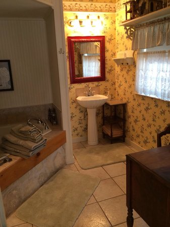 Corner Cottage B&B: Attached bathroom with antique wood vanity table, counter space & large tub