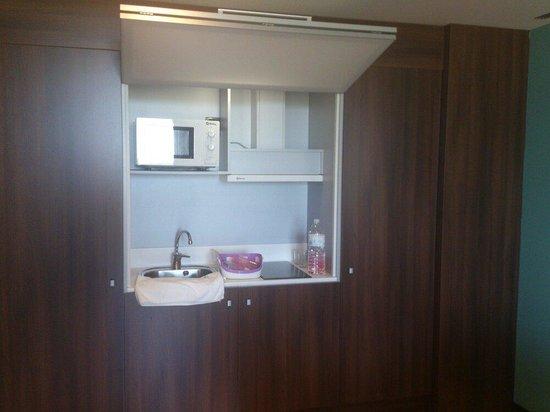 Eurostars Rey Fernando: Cocina con microondas, vitroceramica, fregadera, armarios y nevera grande.