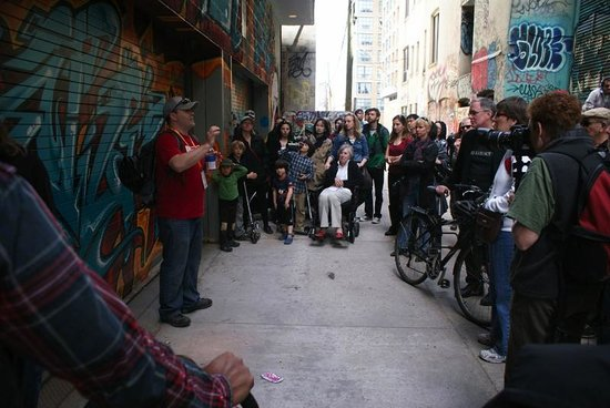 Tour Guys: Tour Guy Jason talks to Jane's Walk participants on a graffiti tour