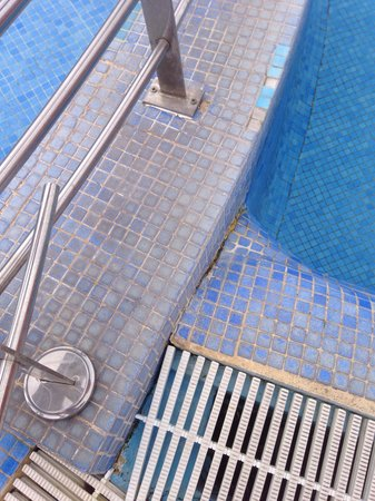 Be Live Experience La Nina: Cracked dirty tiles at poolside
