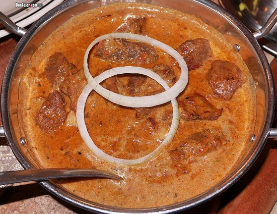 Masala Indian Cuisine: Lamb Madras Diced lamb cooked in mixture of spices and coconut flavoured sauce.