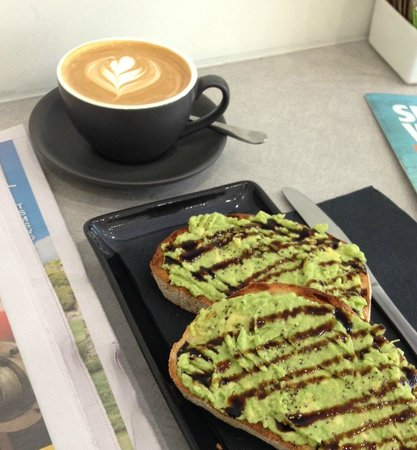 Ad Infinitum Cafe : My flat white and avo toast. Not the best photo sorry. The bread is sourdough. It has balsamic g