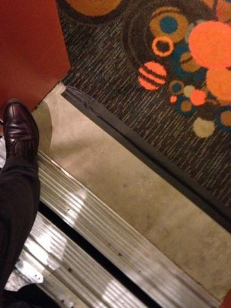 The Curtis Denver - a DoubleTree by Hilton Hotel: bare cement coming off the elevator ... duct tape holding down the carpet