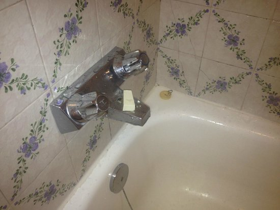 Canadiana Inn: Broken shower lever and dirty bathtub and grout.
