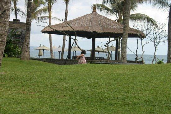 The Legian Bali: halaman hotel yang langsung menghadap pantai, rumput hijau yang segar