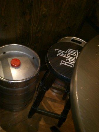 Taberna El Balcon del Tubo : bidones de cerveza rodeando la mesa, la silla encajada entre ellos