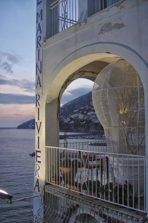 """Hotel Marina Riviera : Breakfast terrace viewed from lounge area - """"light bulb"""" is a cage with half a dozen chirpy budg"""